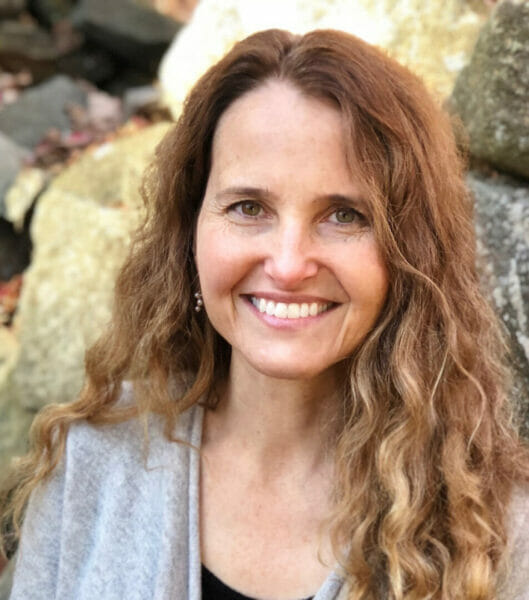 Mara Bishop, author, shamanic teacher and counselor, energy healer, and intuitive consultant, outside in nature near old stone walls with fall red maple leaves