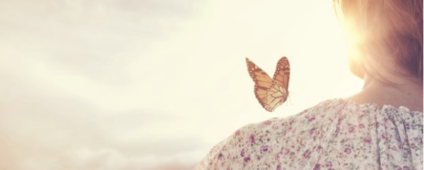 Image from Aspire Magazine article: butterfly on woman's shoulder with golden background. Are you Stagnating or Cocooning?